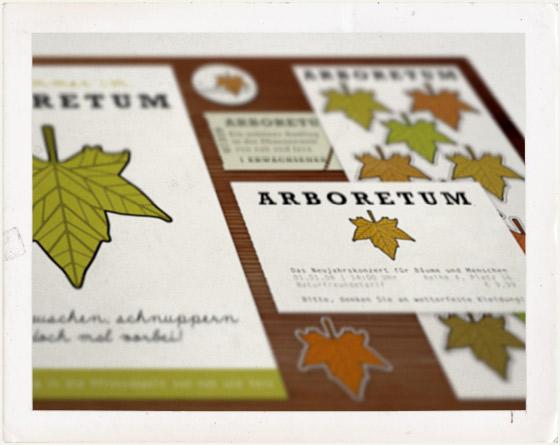 Foto von Plakaten, Eintrittskarten, Visitenkarten, Aufklebern und Buttons des Arboretums mit dem Blatt einer Platane als Logo