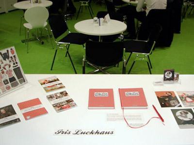 Foto vom Tisch mit der kleinen Ausstellung zu Die wunderbare Welt der Lily Lux, Notizbuch, Kühlschrankmagneten, Vistenkarten und Postkarten mit Aschenbrödel am See, Wintermädchen, Eisläuferin und Weihnachtsengel auf der Frankfurter Buchmesse