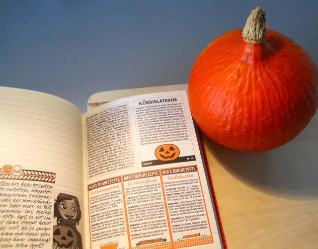 Foto von einem Hokkaido-Kürbis mit dem Lily Lux Notzibuch und den Rezepten für Kürbissuppe, Kürbisauflauf, Ofenkürbis und Kürbiskuchen sowie einer Anleitung zum Schnitzen von Kürbisköpfen