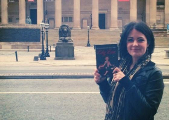 Foto von Ms Jinx mit dem Buch Die wunderbare Welt der Lily Lux vor der St. Georger Hall in Liverpool