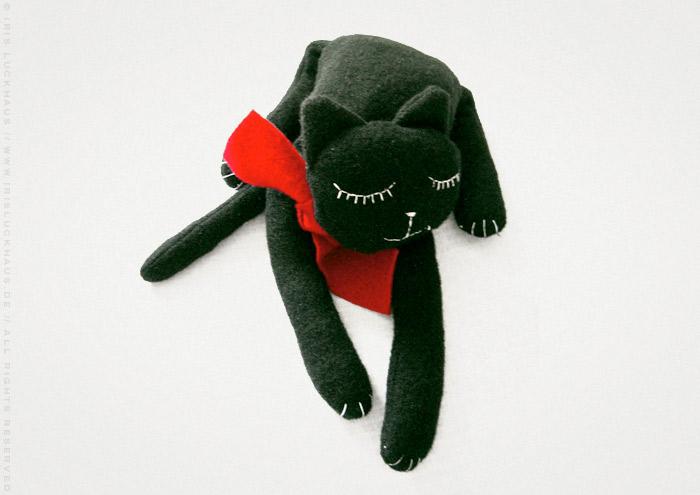 Kuscheliges Stofftier Pauline, eine glücklich schlafende Katze aus Stoff mit einem roten Schal von Iris Luckhaus