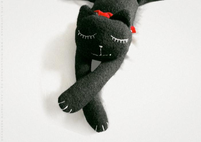 Kuscheliges Stofftier Pauline, eine glücklich schlafende Katze aus Stoff mit einem roten Schal