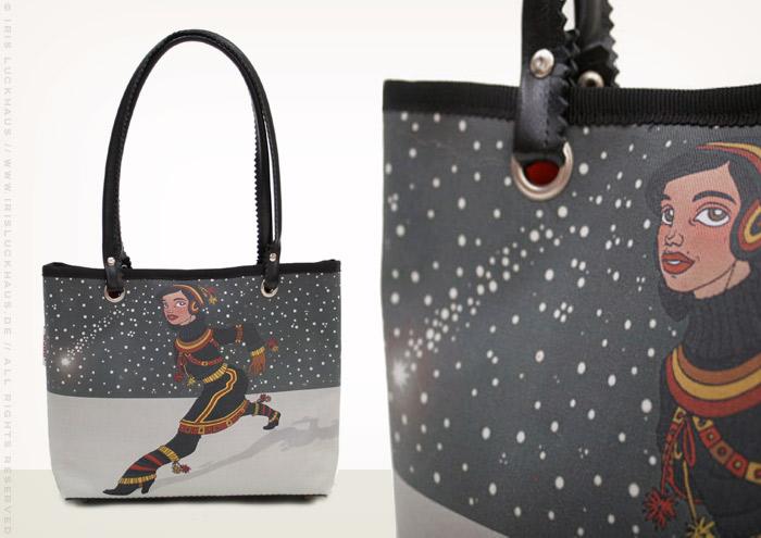 Foto der Tasche mit der Zeichnung von einem Mädchen in Sami Tracht, das vor einem Himmel voller Schneeflocken und Sternschnuppen in großen Schritten über einen gefrorenen See im Winter geht