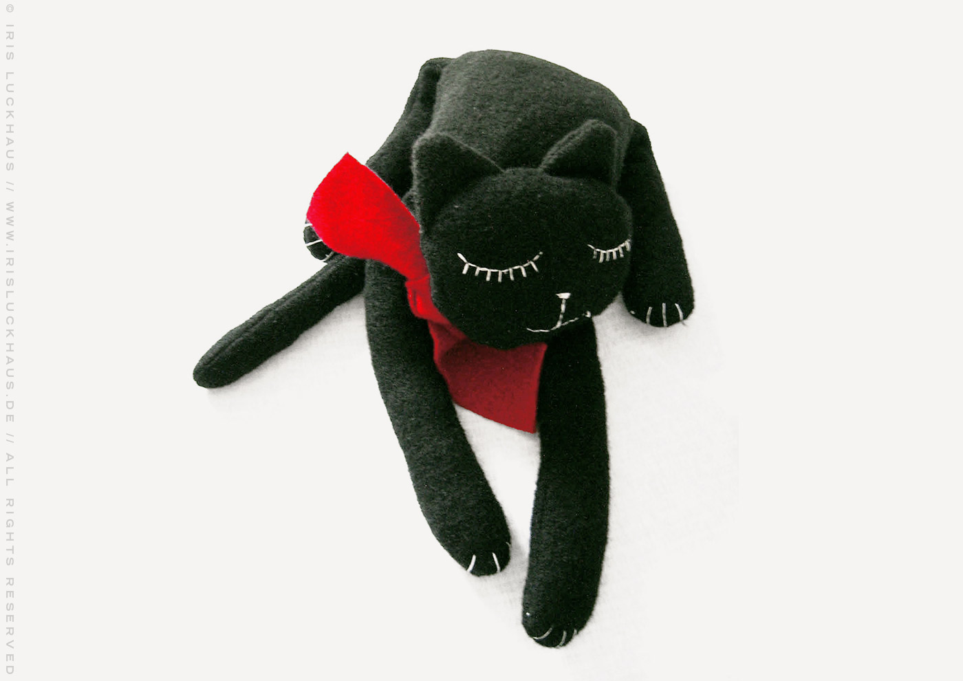 Kuscheliges Stofftier Pauline, eine glücklich schlafende Katze zum Kuschen aus Wirkloden Stoff mit einem roten Schal, Stoffkatze