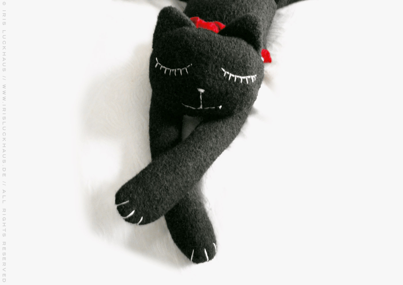 Kuscheliges Stofftier Pauline, eine glücklich schlafende Katze zum Kuschen aus Wirkloden Stoff mit einem roten Schal